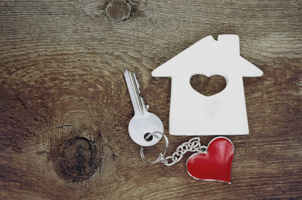 small house and a key with a keychain in shape of heart